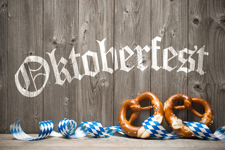 octoberfest: Bavarian pretzels with ribbon on wooden board. Background for Oktoberfest