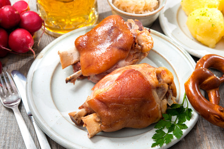 Appetizing Bavarian roast pork knuckle with dumplings and pretzel photo