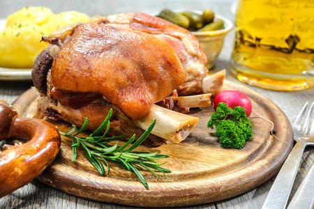 Appetizing Bavarian roast pork knuckle on cutting board Reklamní fotografie
