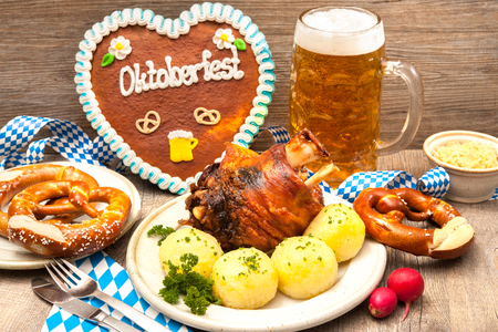 Appetizing Bavarian roast pork knuckle with dumplings and pretzel