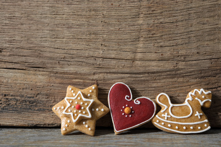 Christmas gingerbread cookies on old wooden background photo