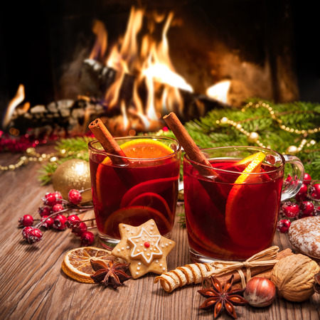diciembre: Dos vasos de vino caliente con la decoración de Navidad en la chimenea romántica