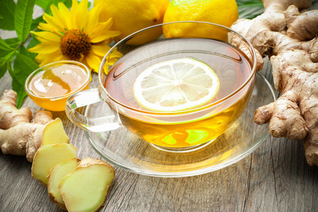 Cup of ginger tea with lemon on wooden table photo