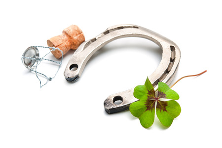 fourleaved: Horseshoe and champagne cork with a four leaf clover isolated on white Stock Photo