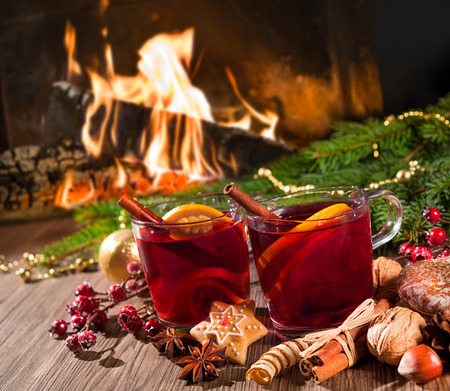 romantic evening with wine: Two glasses of  mulled wine with christmas decoration at romantic fireplace