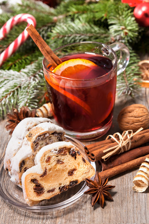 Glass of red mulled wine on table with candy and christmas decorations photo