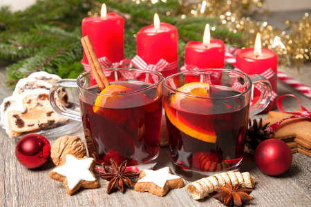 Glasses of red mulled wine on table with burning candles and christmas decorations photo