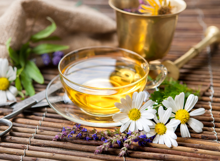 head home: Cup of herbal tea with chamomile flowers on wooden background