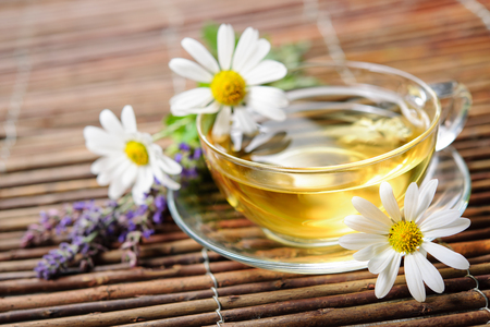 Cup of herbal tea with chamomile flowers on wooden background photo