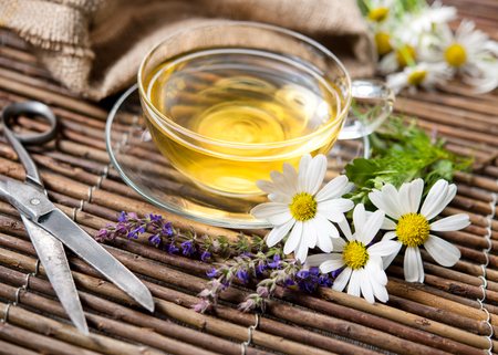 chamomile tea: Cup of herbal tea with chamomile flowers on wooden background