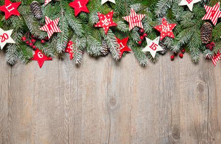 december kalender: Dennenboom takken en adventskalender sterren op oude houten plank