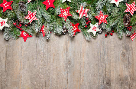 Fir tree  branches and advent calendar stars on old wooden board photo