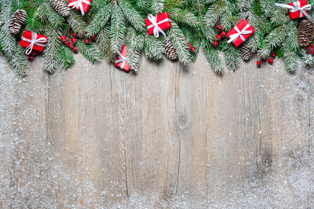 Fir tree branches with christmas gift boxes on old wooden board