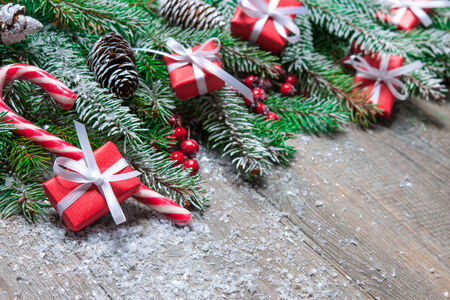 fir cones: Fir tree branches with christmas gift boxes on old wooden board