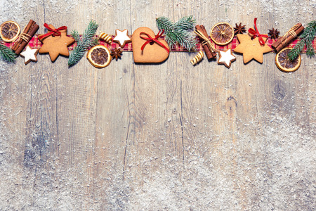 Christmas background with cookies, fir branches and spices on the old grunge wooden board Banco de Imagens