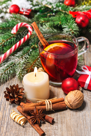 weihnachtsmarkt: Glass of red mulled wine on table with with burning candle and christmas decorations Stock Photo
