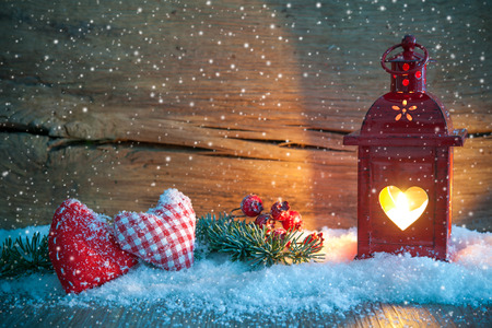 Christmas lantern with textile hearts and snow on vintage wooden background in night photo