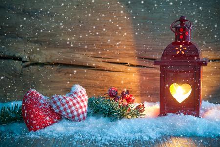 Kerst lantaarn met textiel hartjes en sneeuw op vintage houten achtergrond in de nacht