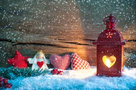Fond de Noël avec la lanterne brûlant dans la neige