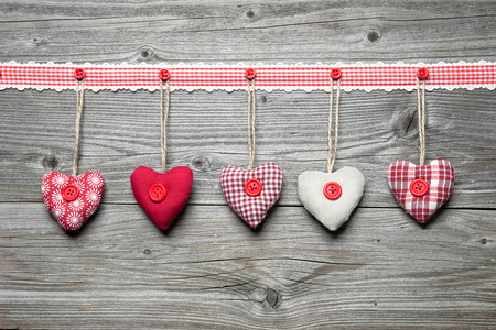 Red hearts hanging over old wood background photo