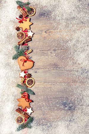 fir: Christmas background with cookies, fir branches and spices on the old grunge wooden board Stock Photo