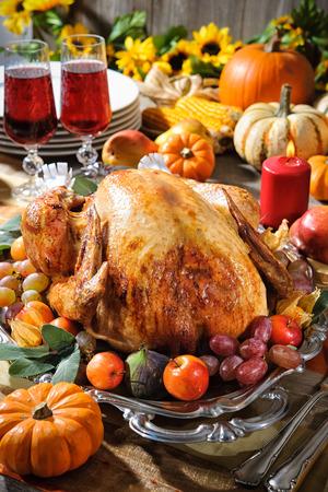 food on table: La cena del Ringraziamento. Tacchino arrosto sulla tavola vacanza con zucche, fiori e vino