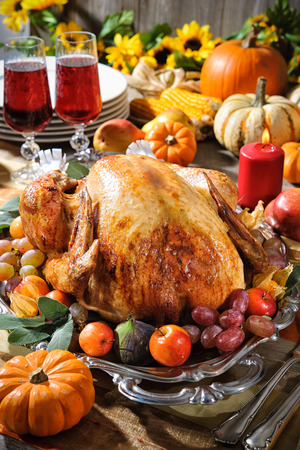 holiday table: Thanksgiving dinner. Roasted turkey on holiday table with pumpkins, flowers and wine