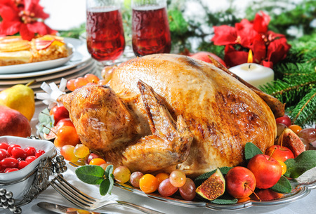 Roasted turkey on holiday table, candles and Christmas tree with ornaments photo