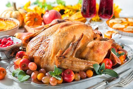 pavo: La cena de Acción de Gracias. Pavo asado en la mesa de fiesta con las calabazas, flores y vino Foto de archivo