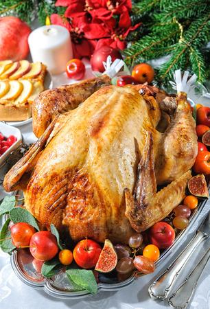 högtider: Rostad kalkon på semester bord, ljus och julgran med smycken