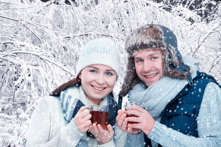 grog: Romantic young couple drinking mulled wine in front of snowy forest