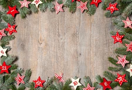 Dennenboom takken en adventskalender sterren op oude houten plank