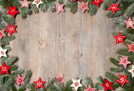 advent season: Fir tree  branches and advent calendar stars on old wooden board Stock Photo