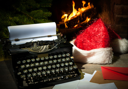 old desk: Old typewriter and Santa Claus hat on desk in front of fireplace