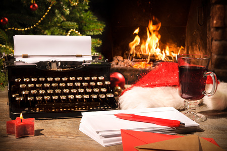 person writing: Old typewriter and Santa Claus hat on desk in front of fireplace
