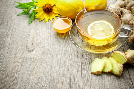 Cup of ginger tea with honey and lemon on wooden table photo