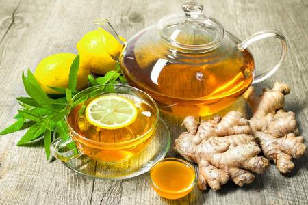 Taza de té de jengibre con miel y limón en la mesa de madera