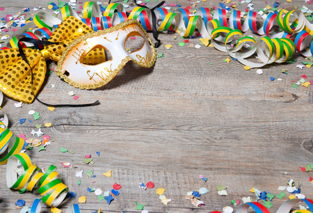 party time: Colorful carnival background with garlands, streamer, party hats, confetti and mask