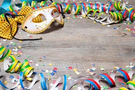 carnival masks: Colorful carnival background with garlands, streamer, party hats, confetti and mask