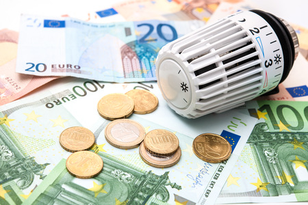 economizing: Heating thermostat with money, expensive heating costs concept Stock Photo