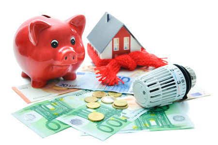 save: Heating thermostat with piggy bank and money, expensive heating costs concept
