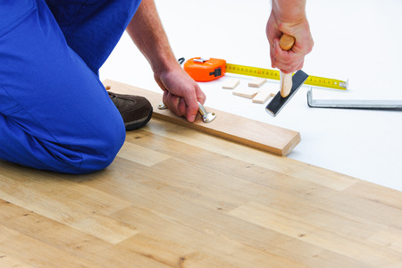 wood floor: carpenter worker installing laminate flooring in the room Stock Photo