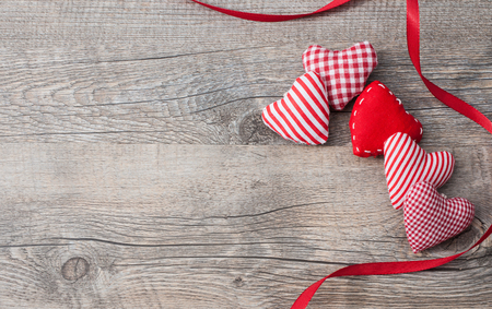 valentine's day: Valentines Day background with patterned textile hearts on old wooden Stock Photo