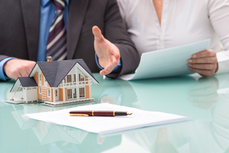 agente comercial: La discusión con un agente de bienes raíces en la oficina
