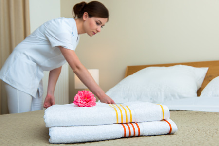 hotel suite: Hotel room service. Young maid changing bedclothes in a room