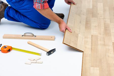 carpenter worker installing laminate flooring in the room photo