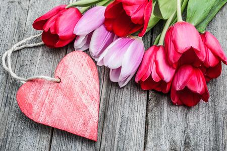 tulipan: Bukiet tulipanów z pustą tagu i czerwonym sercem na tle drewnianych