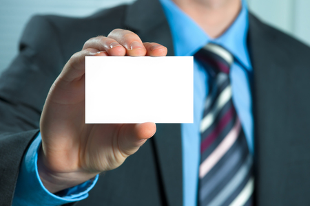 Business man in suit showing his business card