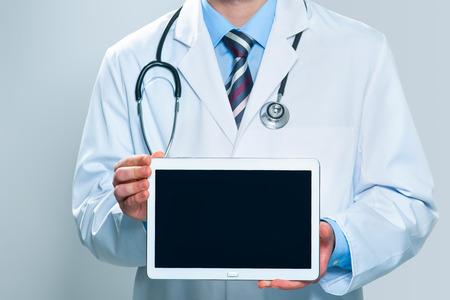 白い背景上に分離されて空白のデジタル タブレットを保持している医者 写真素材