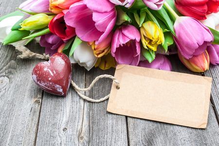 空のタグと木製の背景に赤いハートとチューリップの花束